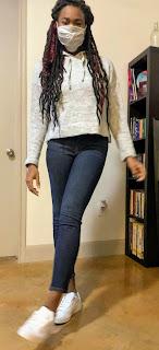 Modeling grey sweatshirt, jean, and white sneakers