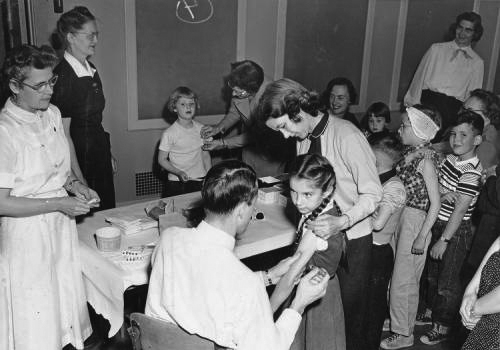 Dr. William H. Sippel administers the polio vaccine to children at Emerson School, Bozeman, 1954.