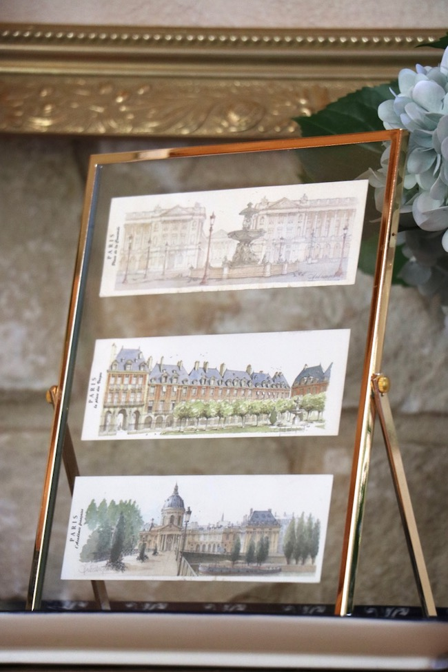 A whitestone wall  visible through a floating glass frame is reminiscent of old Paris architecture