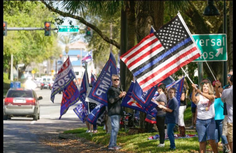 Partidarios del expresidente Donald Trump ondean banderas afuera del centro de convenciones de Orlando, Florida, donde se realiza la Conferencia de Conservadores de Acción Política, CPAC, el domingo 28 de febrero de 2021 / AP