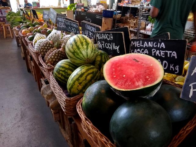 A stand with different fruits, like watermelon, pineapple, papaya, mango, avocado and banana.