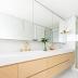 Banheiro todo branco com metais dourados e armário em lâmina de madeira clara!