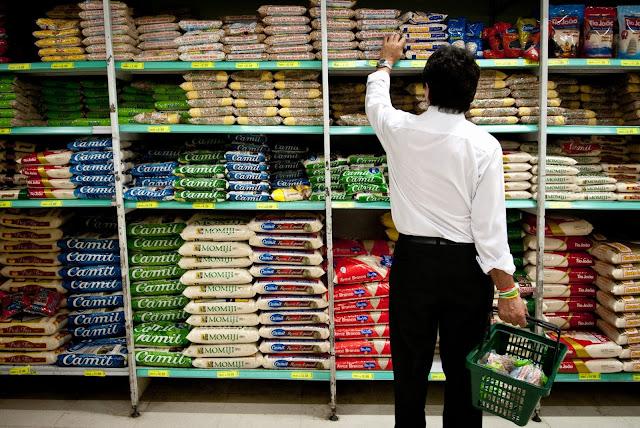Homem de costas para a câmera escolhendo um pacote de feijão em uma prateleira de supermercado com várias marcas de arroz e feijão diferentes