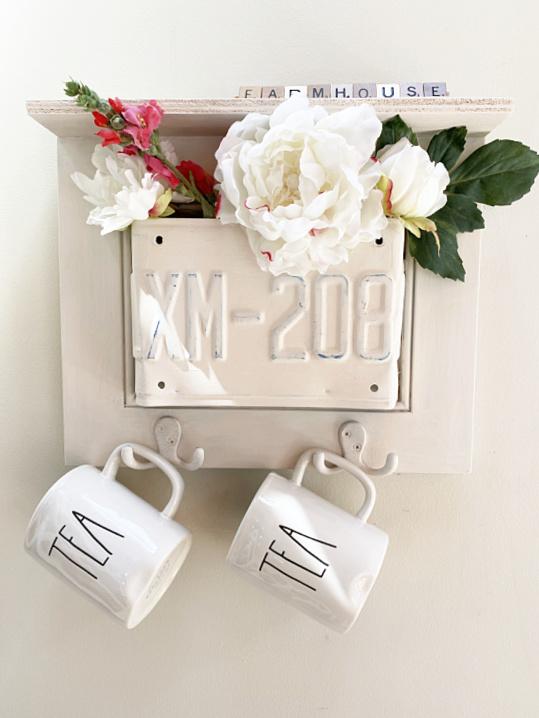 cabinet shelf with flowers and hooks holding mugs