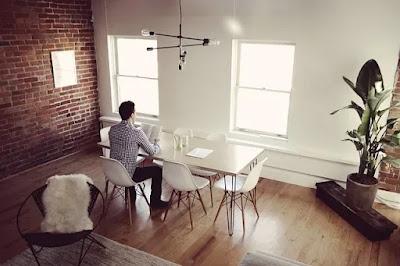 Foto imagem de um apartamento com parede de tijolos a vista, amplas janelas brancas envidraçadas, piso em madeira onde temos uma mesa com um estudante universitário sentado em uma cadeira branca utilizando seu notebook.