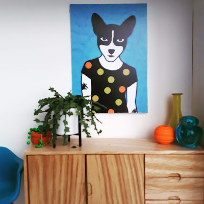 1/12 scale modern miniature scene of a wooden mid-cantury modern sideboard with a string of pearls and an ivy plant on top at one end, and three vases in yellow, orange and teal at the other. Above the sideboard is a print of an animal waering a spotty T shirt in the same colours.