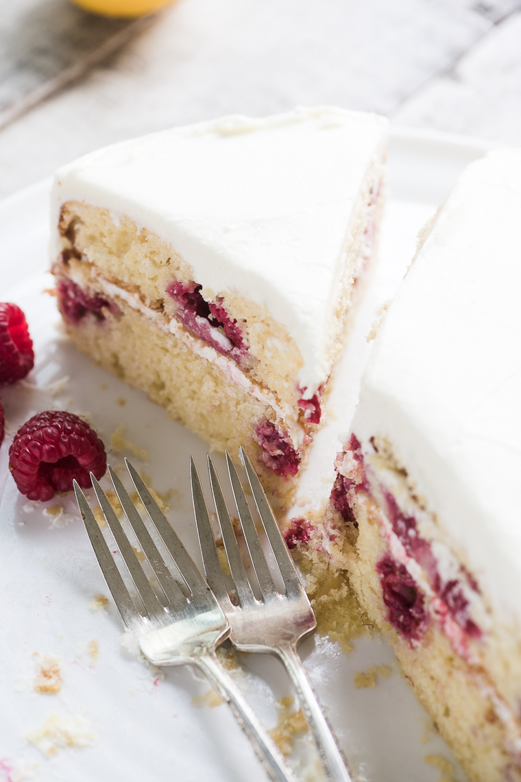 An old fashioned Raspberry Lemon Cake recipe with lemon buttercream frosting, made with yogurt, fresh raspberries, and lots of lemon juice for a sweet/tart delicious dessert.