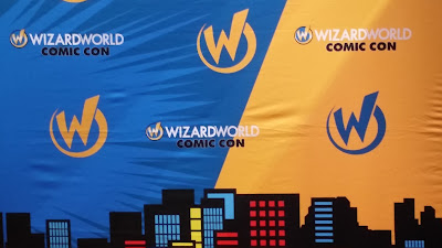 A backdrop with the Wizard World Comic Con Logo and the silhouette of a city.