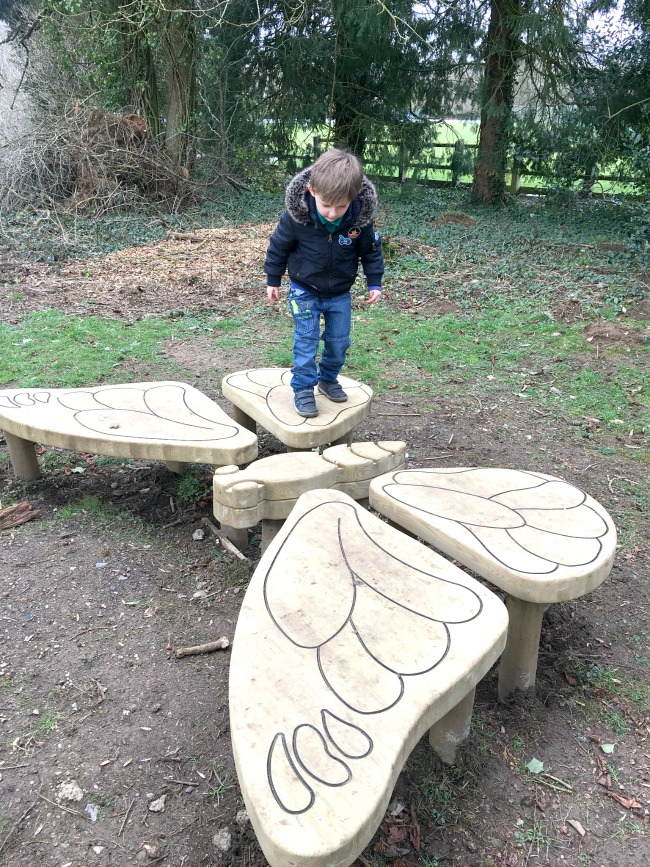 boy-walking-on-wooden-butterfly-sculpture