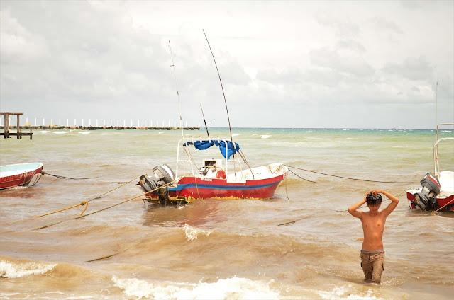 Playa del Carmen con un niño saliendo del agua, Mexico.