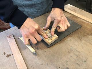 四角い粘土の板にハンコをおしえている写真