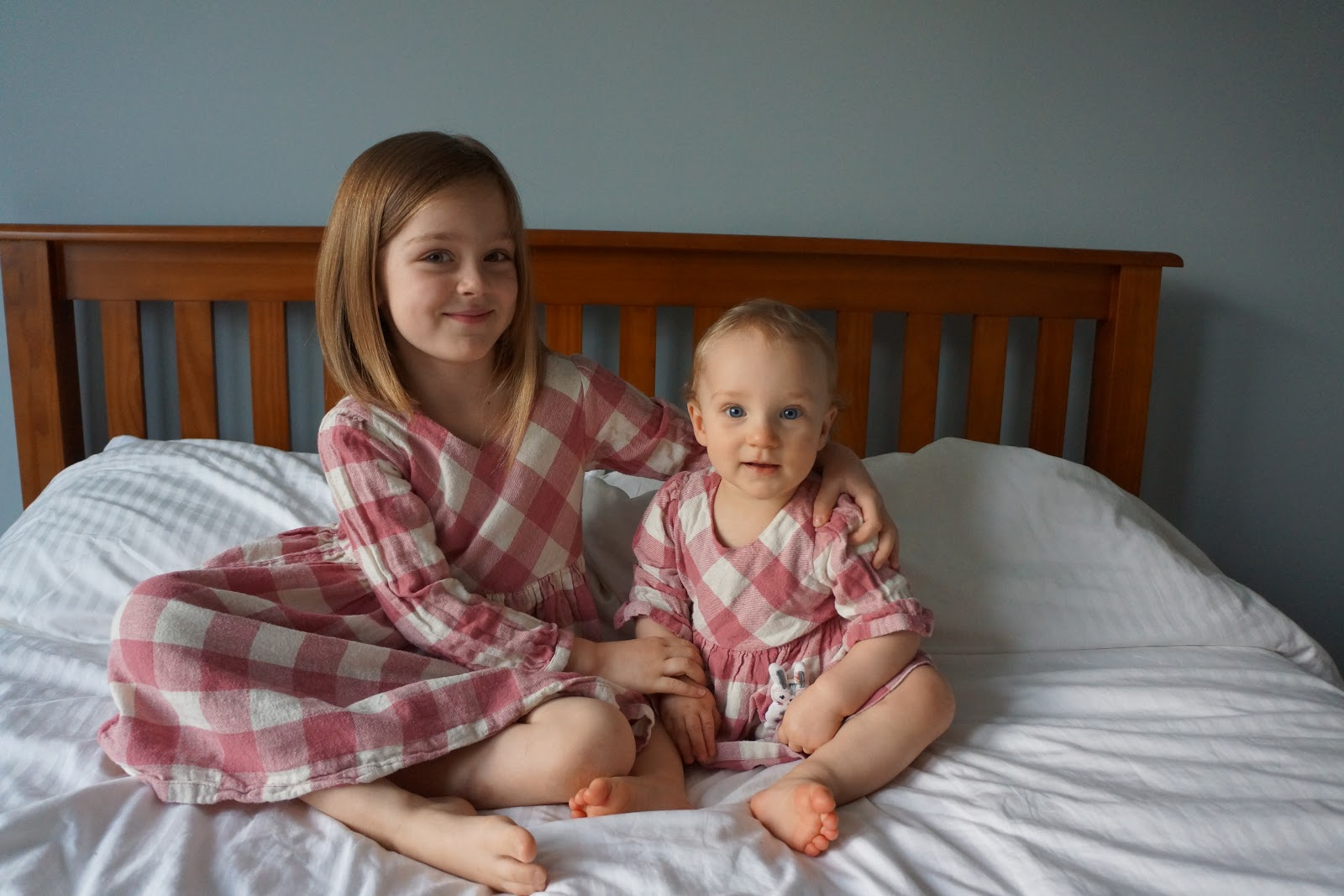 baby and sister in matching outfits smiling on bed