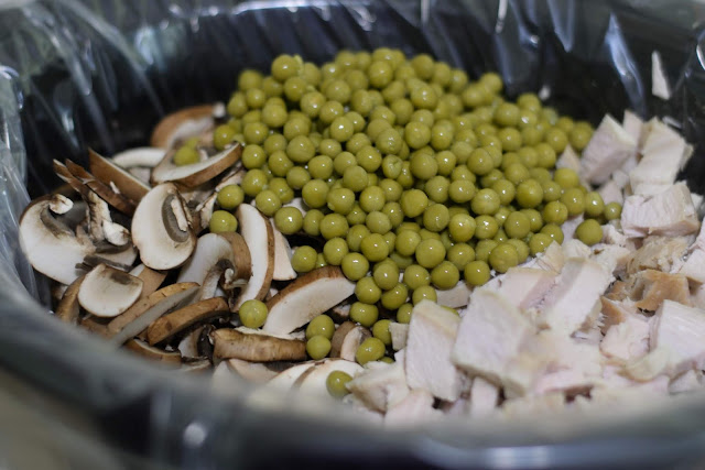 The turkey, peas, and mushrooms in the crockpot.