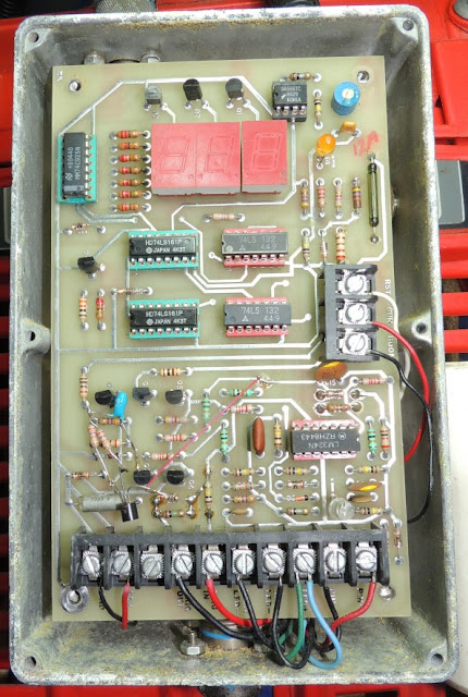 Interior of front aluminum box showing main circuit board with seven chips, ten transistors and wires attached to terminals on the edges