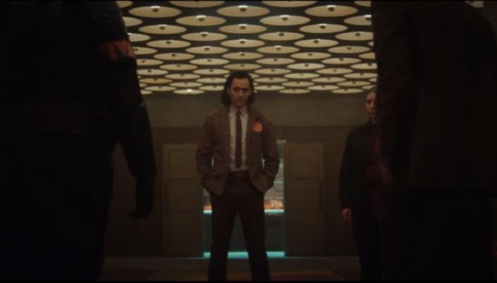 Imagem: Loki (homem branco de cabelo preto na altura do ombro e usa casaco marrom claro, blusa e calça social e gravata) está parado no centro de uma sala com as mãos no bolso. A sua frente tem a silhueta de guardas.