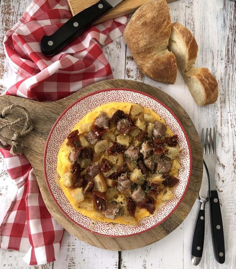 Tortilla abierta con butifarra, tomate confitado y pan tostado