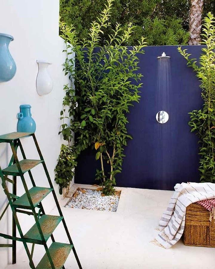 Ducha exterior delante de pared azul añil