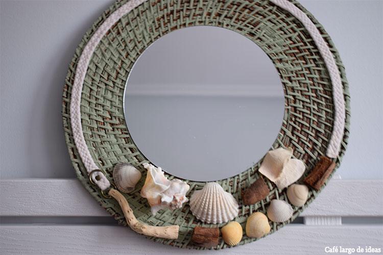 espejo con caracolas, conchas y palos