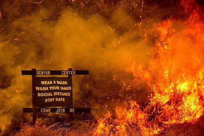 "California wildfire over sign for ""Senior Center: Wear a mask. Wash your hands. Social distance. Stay safe. Come join us."""