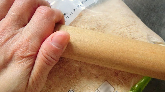 ビスケットを袋に入れたまま麺棒で細かく砕きます