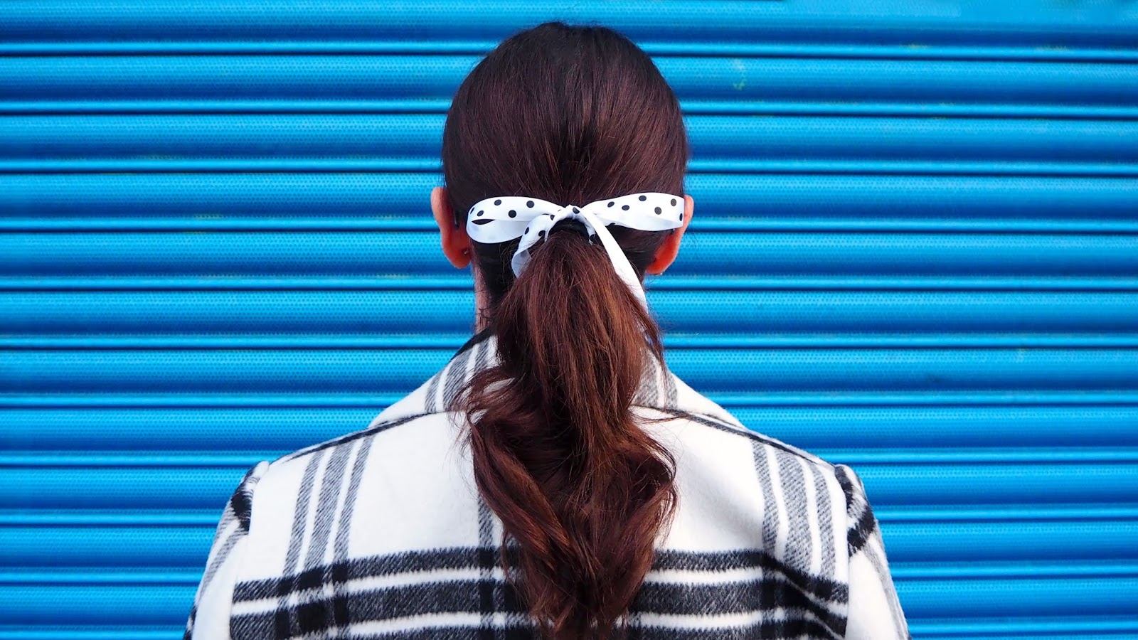 black and white polka dot ribbon on brown hair ponytail and black & white checked coat in front of a blue wall