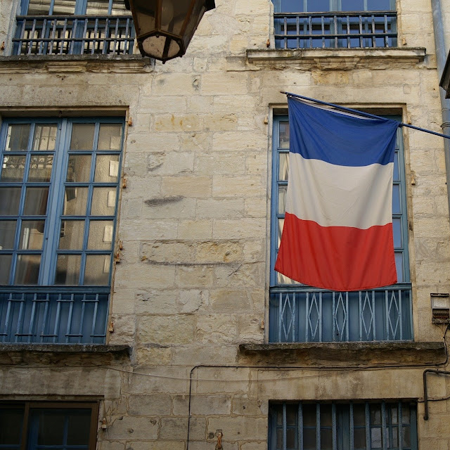 french flag and old building