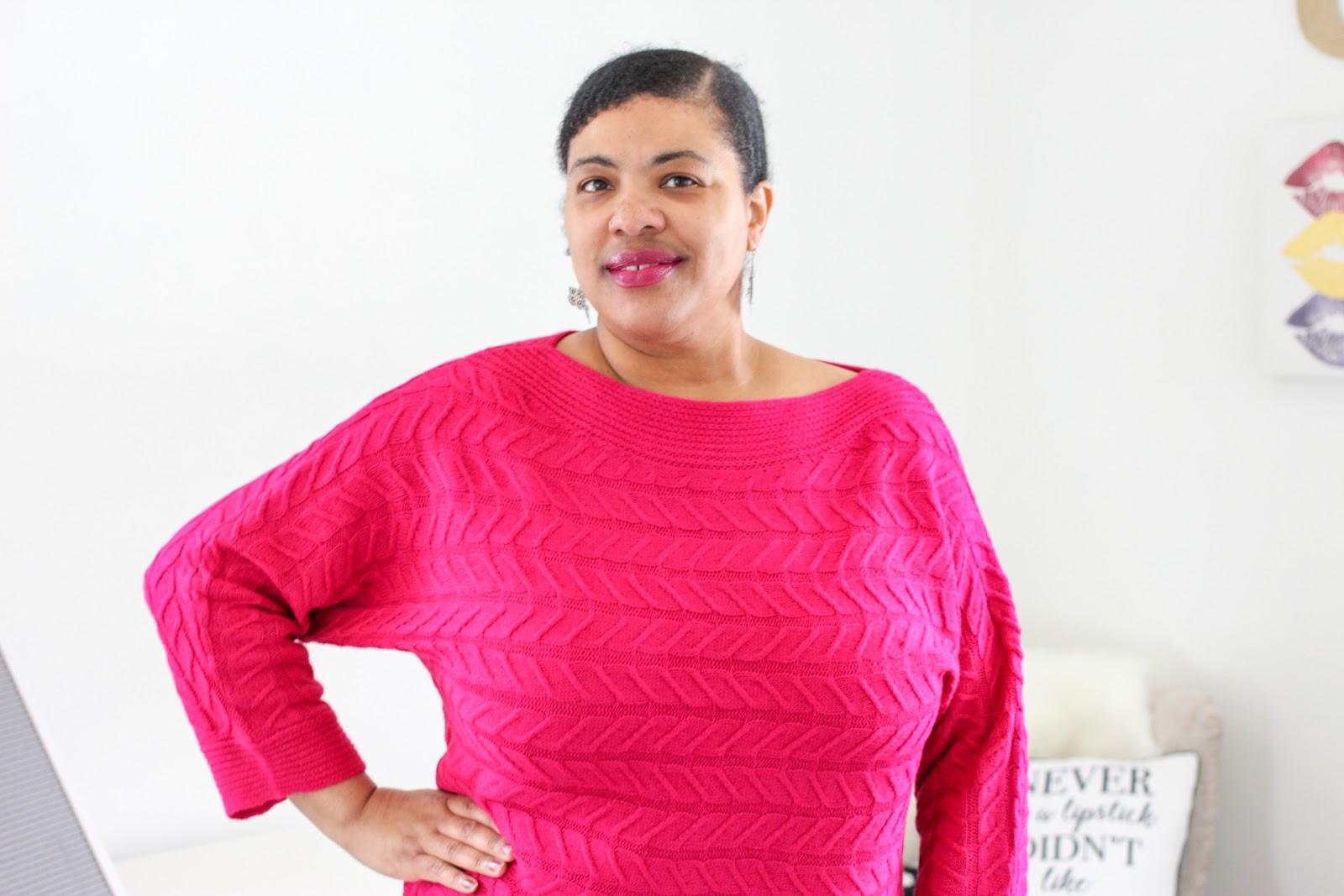 a black woman wearing a hot pink sweater