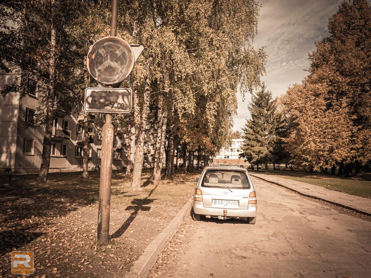 Ar krāsu aizkrāsota ceļa zīme un mašīna ceļa malā