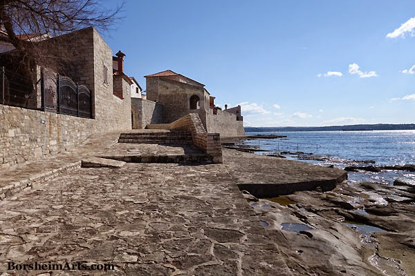 The Adriatic Sea meets the old stone wall in Novigrad, Croatia