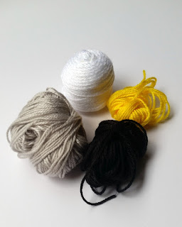 4 wound balls of 4 ply weight acrylic laid out in a diamond formation. Clockwise from top: white, yellow, black, silver on a white background.