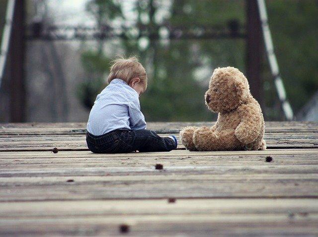 seorang anak kecil yang lucu sedang duduk berhadapan dengan boneka kesayangannya