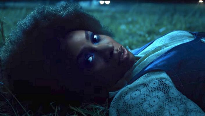 Imagem: a personagem Monica Rambeau, uma mulher negra, olhando diretamente para a frente, caída num gramado escuro.