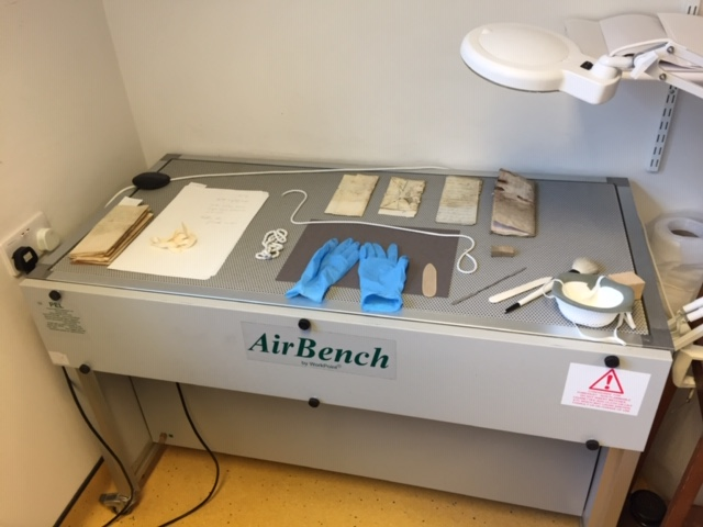 Mould documents on a perforated air bench waiting to be cleaned. Also on the table are nitrile gloves, a mask, various snake weights, brushes and spatulas.