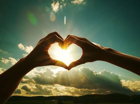 Duas mãos que se unem e formam um coração. Ao fundo, um lindo céu com nuvens brancas e um brilho intenso do sol no centro.