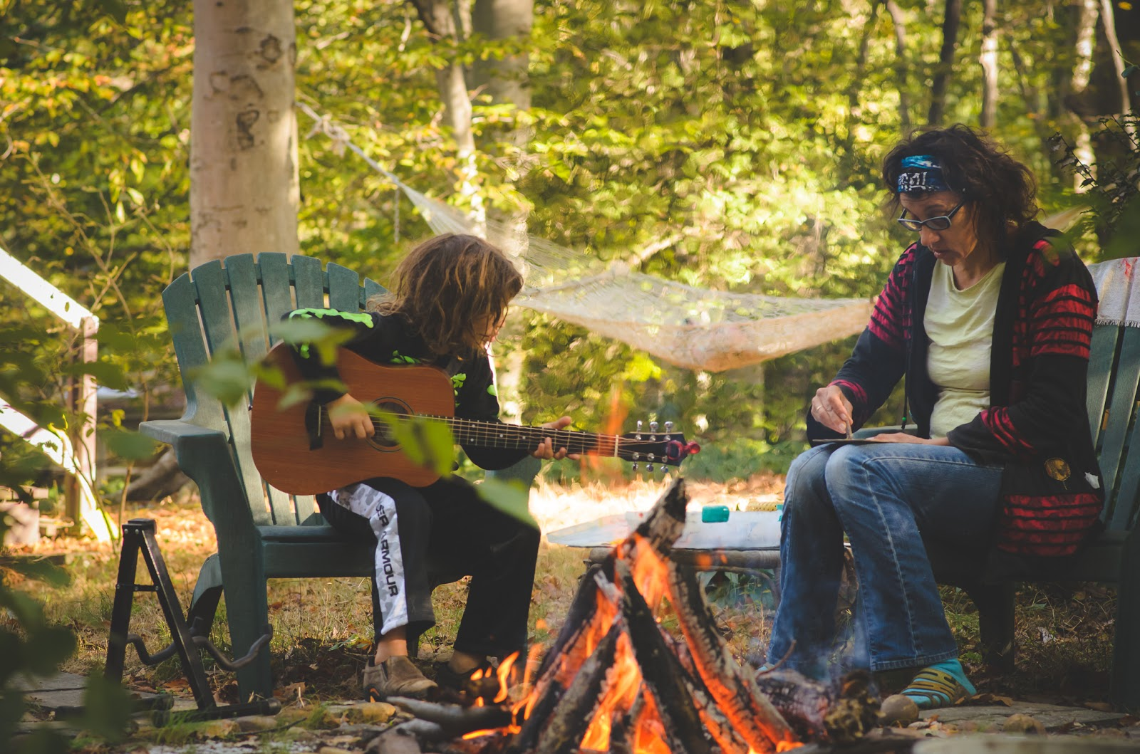 mother and son playing guitar and drawing in front of campfire ©Diana Sherblom Photography