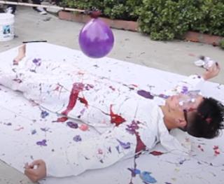 Liegender Mann wird mit farbgefüllten Luftballons beworfen als Kunstobjekt.