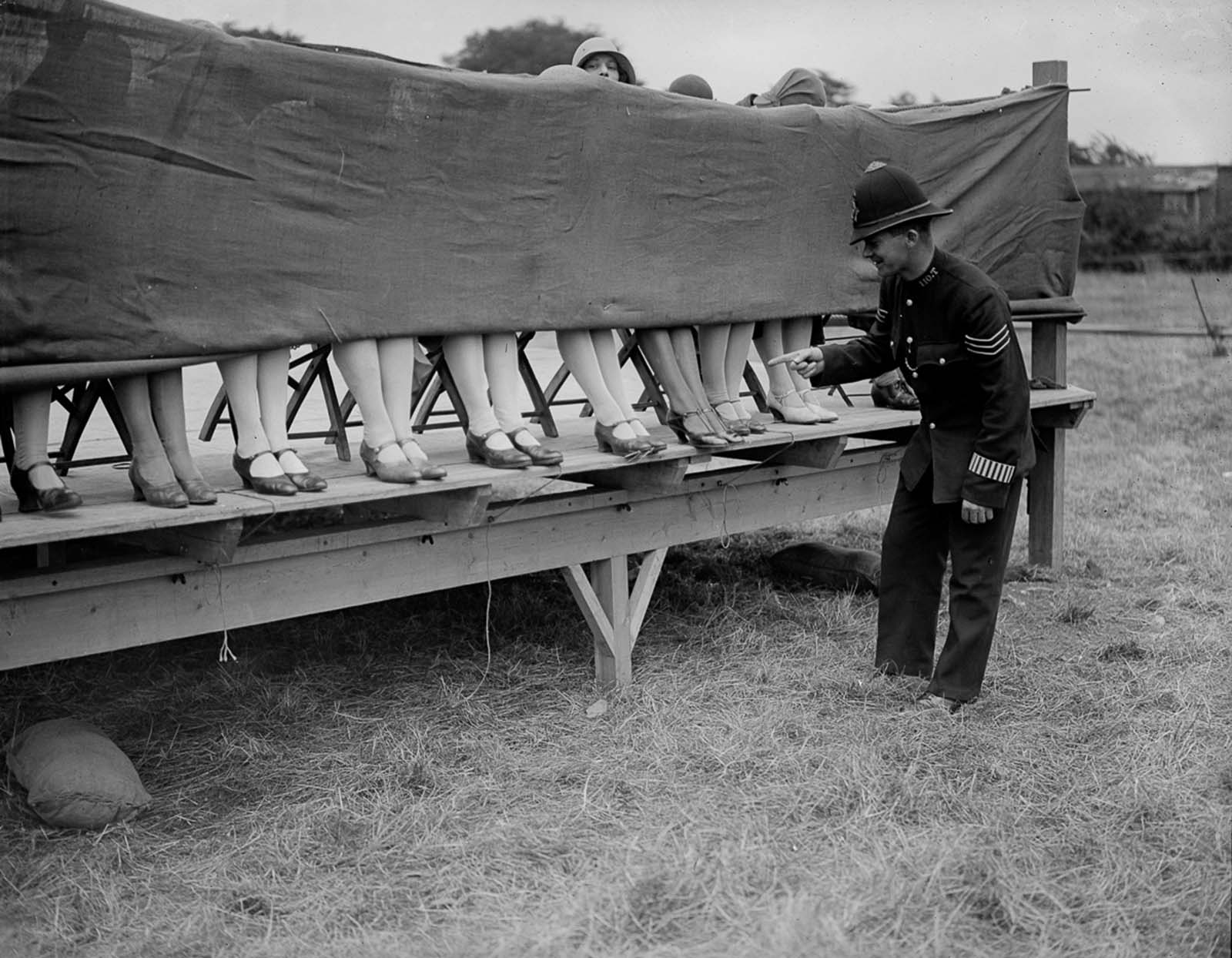 A policeman judges an ankle competition at Hounslow, London. 1930.