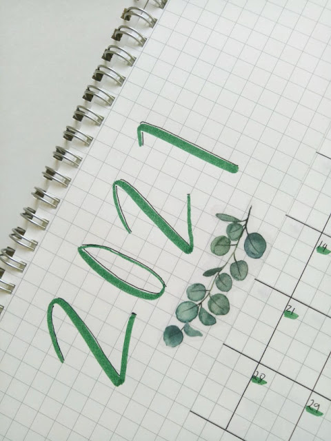 Bullet Journal for 2021, written in green with a leaf sticker on a grid notebook