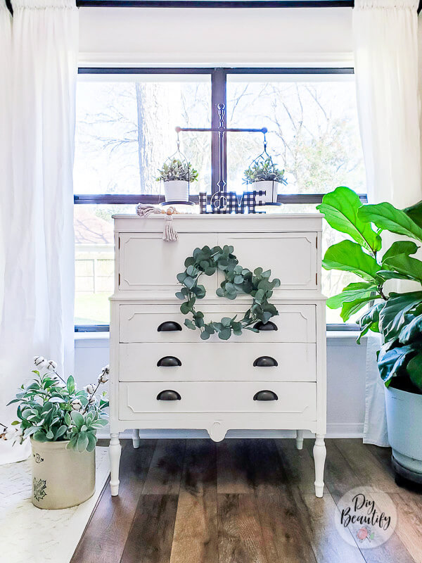 white cottage dresser and greenery