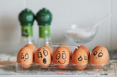 Pcture of eggs in a clear carton with funny faces drawn on them. Food For swimming. Are eggs risky for your heart health?