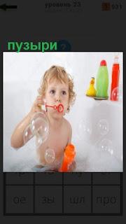 в ванной сидит ребенок и пускает мыльные пузыри