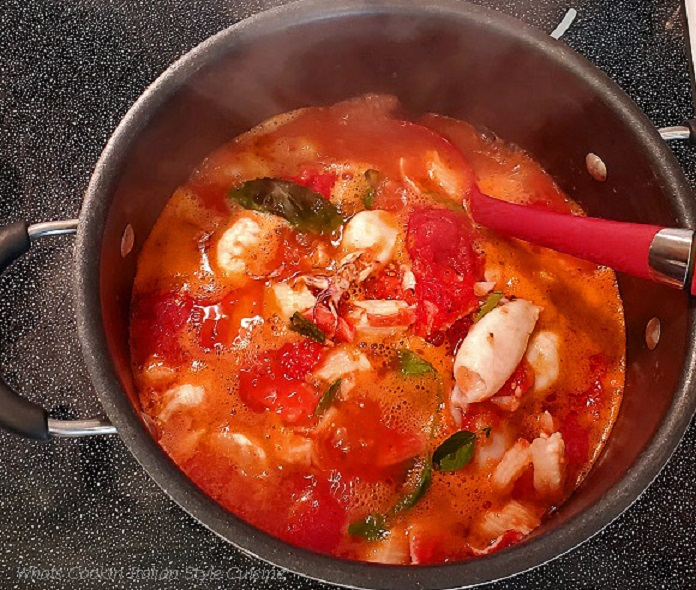 this is a big pot of tomato sauce with all kinds of fresh seafood in the pot including on top is calamari, scallops, crab, shrimp and haddock