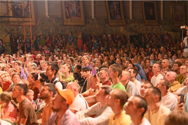 A sea of devotees in the huge main pandal, surrounded by banners depicting the importance of hearing, chanting, and sadhu-sanga