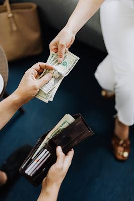 شخص يعطي أو يدفع المال وآخر يأخذه منه بيده