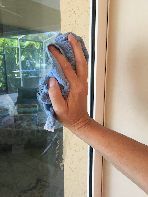 Hand with blue microfiber cloth cleaning window