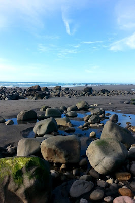 Large rocks on a New Zealand black-sand beach at low tide.