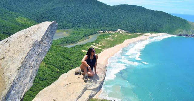 mulher sentada em uma pedra com o mar ao fundo