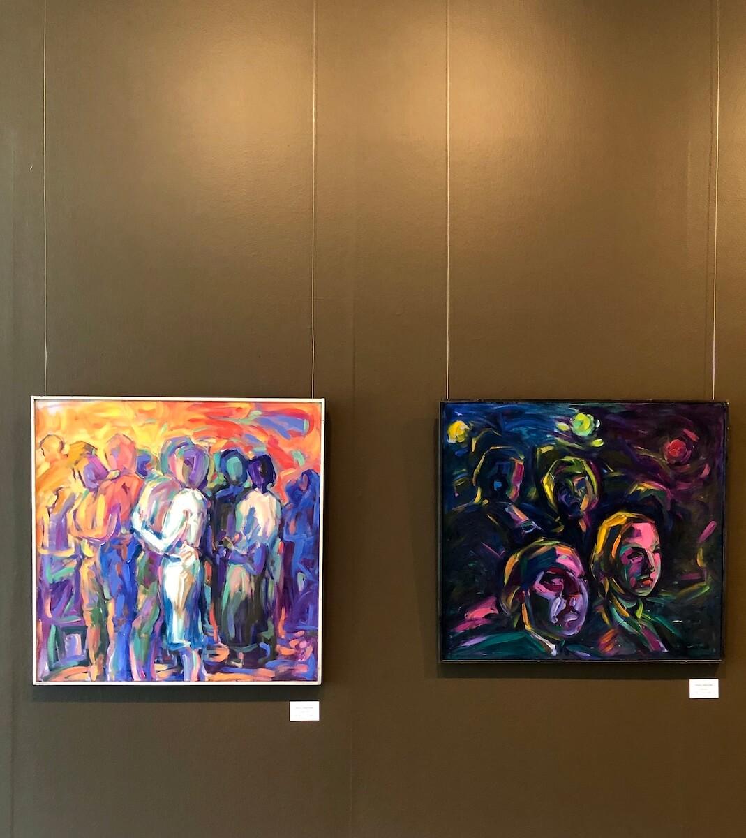 Kuvassa näkyy kaksi Hannu Nikanderin öljyvärimaalausta, joissa on värikkäitä hahmoja. Vasemman reunimmaisessa öljyvärimaalauksessa hahmot näyttävät tanssivan. Oikean reunimmaisessa maalauksessa hahmot ovat teoksen nimen mukaisesti ikäänkuin katsomossa.