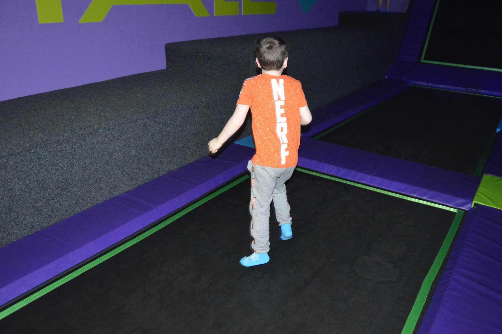 boy standing in a trampoline park