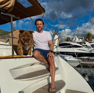 Martin Henderson sitting in a boat with his dog